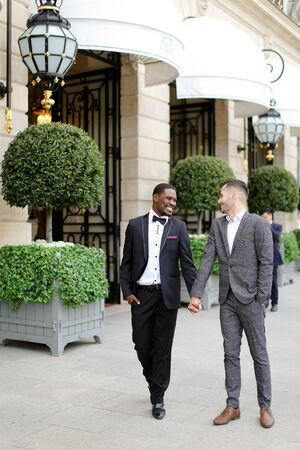 Afro american and caucasian handsome gays walking outside and holding hands in city. Concept of same sex male couple. Banco de Imagens