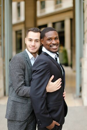 Caucasian man hugging afro american guy outside and wearing suit. Concept of happy same sex couple and gays. Banco de Imagens