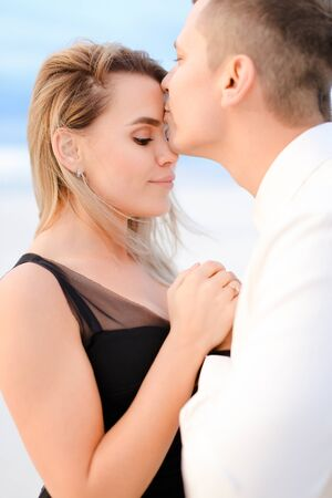 Young man kissing girl in white background. Concept of love.