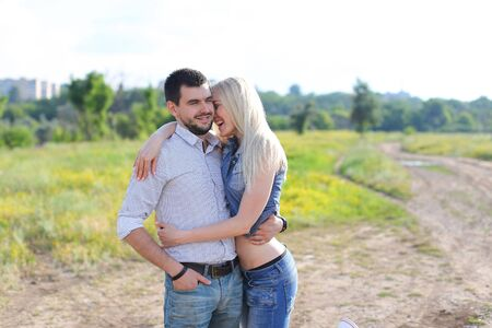Young beautiful couple is embracing a man takes care of a woman happy Stock Photo