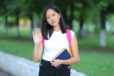 Girl female teenager with black hair in a bob white east Asian woman green park with a backpack background. Lady holds, dials, push your finger, smiling, looking at the camera and waves Foto de archivo