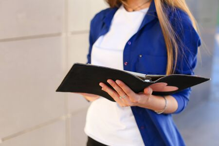 Girl holds in hands diary and black notebook with sheets. Young woman with light brown hair dressed in white T-shirt and bright blue shirt with pocket on arm bracelet.Concept of organization and planning of day, notebook, homework, busy dealer.