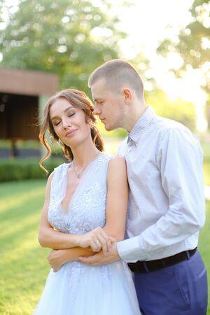 Handsome groom kissing bride outside in garden. Concept of love, wedding and happy couple. Reklamní fotografie