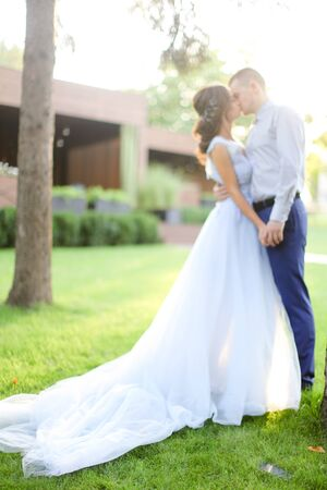 Caucasian fiancee kissing groom in park and wearng white dress. Concept of married couple and bridal photo session in open air.