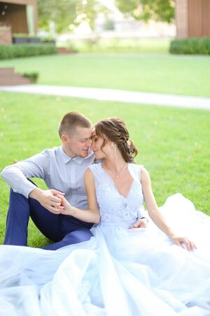 Caucasian pretty bride with groom sitting and kissing on grass in park, wearing white amazing dress. Concept of bridal photo session in open air, beautiful fiancee. Reklamní fotografie - 133335934