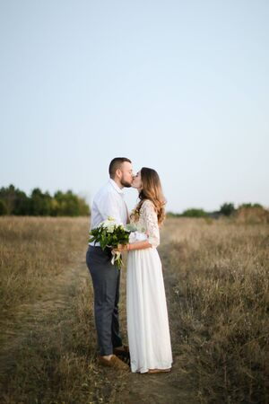 Caucasian groom kissing bride with bouquet of flowers in steppe background. Concept of happy married couple and love. Reklamní fotografie