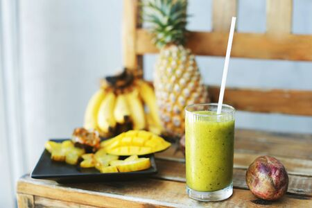 Green juice near bananas with mango, carambola and pine apple on wooden chair. Concept of healthy food and exotic fruits.