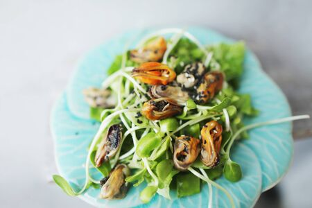 Tasty thai salad with mussels on white plate. Concept of seafood and exotic menu in Thailand.