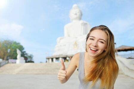happy joyful woman showing thumbs up, background of Big Buddha Phuket, traveling to sunny Thailand. Concept of movement of people in relatively large geographical locations