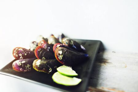 Exotic mussels and sliced lime on black square plate with lime in white background. Concept of healthy seafood and restaurant menu in Thailand. Reklamní fotografie