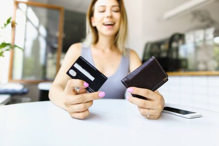 Blonde woman sitting at cafe and keeping wallet. Concept of paying by credit card.