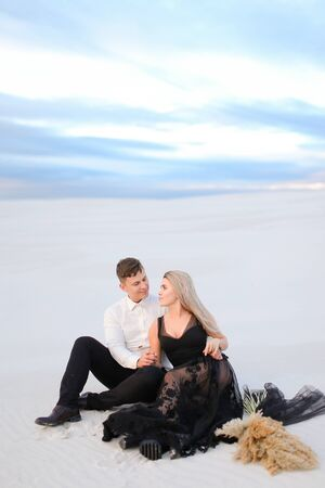 Young happy womanwearing balck dress and man sitting on snow in steppe. Concept of winter photo session and love.