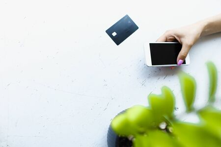 Female caucasian hand keeping smartphone near credit card in white and green leaves background. Concept of purchasing online.