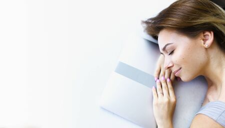 Banner of blonde female freelancer lying on laptop in white background with copy space. Concept of having break and preparing before exam.