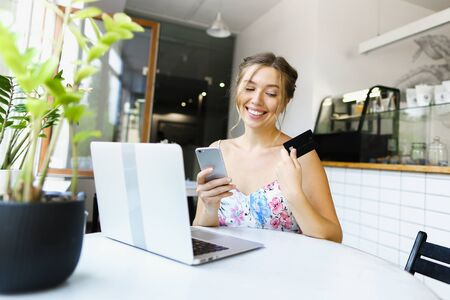 Young happy girl holding smartphone and debit card near laptop. Concept of purchasing goods online and shopping by internet.