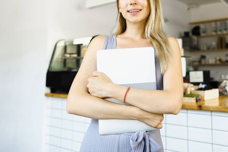 Blonde housewife standing with closed laptop in kitchen and smiling. Concept of happy wife and modern technology.