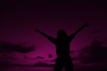 Female black silhouette with raised hands on violet sunset sky background in Hawaii. Concept of summer vacations, freedom and cheap last minute tours to southern countries.