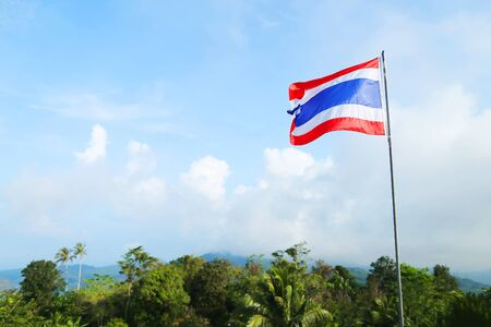 copy space flag of Thailand against blue sky, beautiful green nature and mountains, blue white and red colours. photo taken from the statue of the Big Buddha