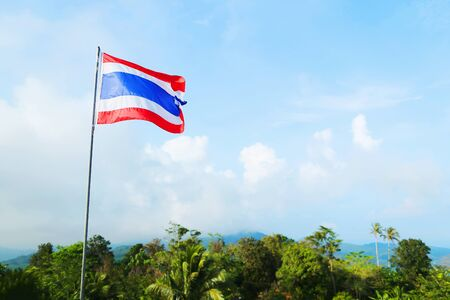 flag of Thailand against blue sky, beautiful green nature and mountains, blue white and red colours. photo taken from the statue of the Big Buddha Reklamní fotografie