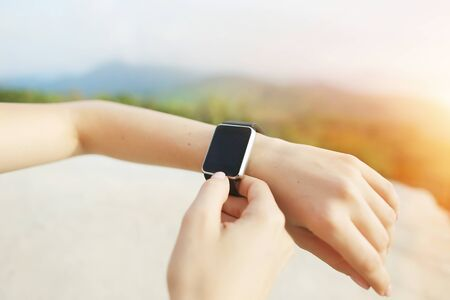 Sunny photo of closeup hands using smartwatch with mountains in background. Concept of modern technology, useful gadget and nature.