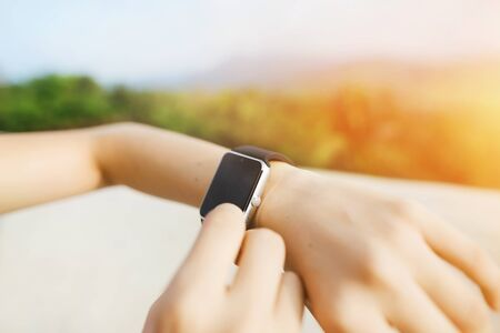 Light photo of closeup hands using smartwatch with mountains in background. Concept of modern technology, useful gadget and nature.