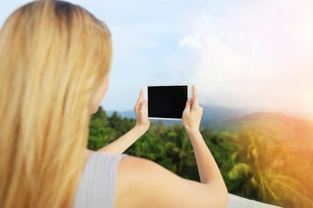 Sunshine photo of blonde woman using tablet and taking photo of Thailand mountains. Concept of summer vacations, last minute tours and modern technology.