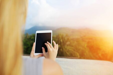 Sunshine photo of female person using tablet and taking photo of Thailand mountains. Concept of summer vacations, last minute tours and modern technology. Reklamní fotografie
