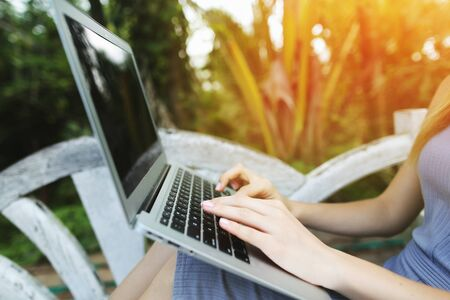 close up woman hand fingers press laptop keyboard for freelancing remote work on sunny day, background of sunshine green palms in Thailand, Phuket. Concept of new technologies for better life, travel to tropical countries Reklamní fotografie