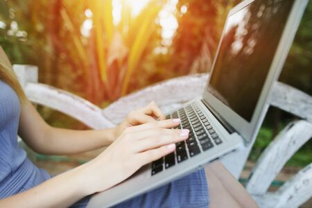 Concept of new technologies for better life, travel to tropical countries. close up woman hand fingers press laptop keyboard for freelancing remote work on sunny day, background of sunshine green palms in Thailand, Phuket. Reklamní fotografie