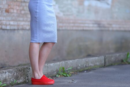Legs girl in red slip-on, one leg bent at knee on background of gray concrete wall of stone. Concept of advertising footwear slipony, comfortable shoes.