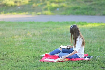 feminine working outdoors with papers in glasses. in the park for a laptop fast food snack and uses a tablet Reklamní fotografie