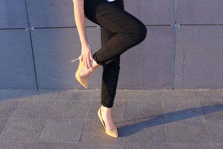 Girl holds leg rotated in profile at camera against background of gray wall of modern business center. Girl dressed in black classic trousers and beige high heels. Concept of advertising, advertising clothes, shooting lookbook, tired feet.