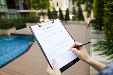 large hand portrait of subscribers sign contract on background of new building with swimming pool. concept of long-term rental housing or short-term apartment rental travel. Front used with Open Font License Reklamní fotografie