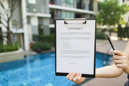 woman is holding pen and contract, proposes to sign document against background of building with apartments. concept of signing papers, travel rental housing. Front used with Open Font License