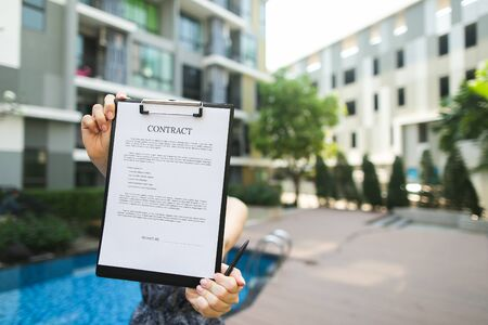 girl is holding contract, Focus on document. young real estate agent offers lease for long term accommodation. concept of long trips. Front used with Open Font License