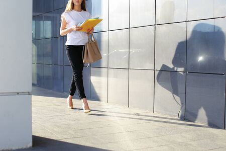 Successful young business woman walks and holds documents in yellow folder on background of gray wall of shopping business center.