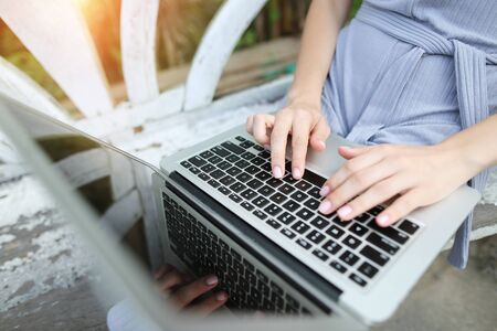 above portrait close up woman hand fingers press laptop keyboard for freelancing remote work on sunny day, background of sunshine green palms in Thailand, Phuket. Concept of new technologies for better life, travel to tropical countries