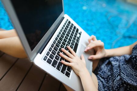 woman and kid Fingers typing on the computer keyboard. Close up portrait of two hands pressing buttons on laptop at sunny day swimming pool. concept of business freelance working, new technologies