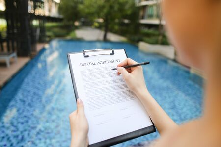 Close-up of girls hand sign document. concept of renting an apartment or car In travel, new contract is an arrangement. Front used with Open Font License