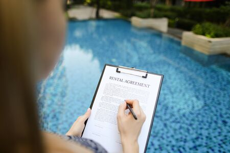 close portrait of signing rental agreement document on background of swimming pool. woman taking apartment for long term. Front used with Open Font License