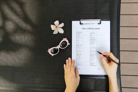 bright flat lay of woman hands fill visa application with pen for travel, sunlight portrait with sunglasses and flower. concept of traveling journey. Front used with Open Font License