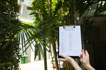 Focus on document, girl fills out visa application form against background of palms and sun and is going to travel to Australia. concept of assistance agencies in preparation of documents, agreements between people or provision of tourist services. Front used with Open Font License