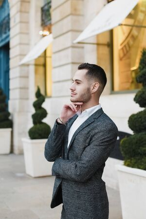 Young cacuasian male person wearing suit standing near building outdoors. Concept of fashion and businessman, urban life.