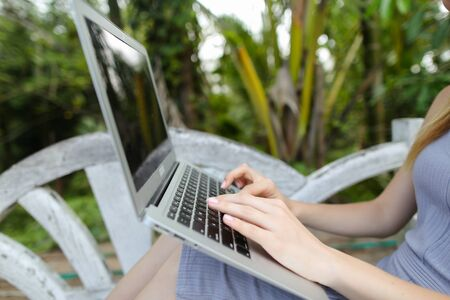 Female person using laptop, palms in background. Concept of exotic summer vacations and modern technology.