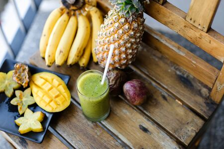 Nice pine apple with bananas, carambola and mango standing on wooden chair, kiwi fresh juice. Concept of healthy food and exotic diet.