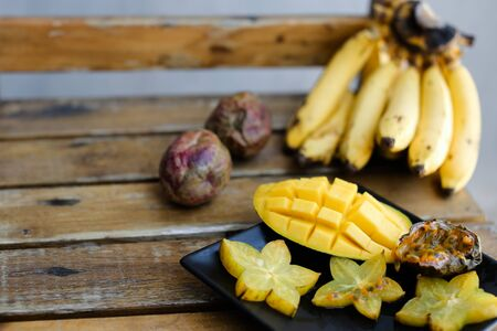 Close up tasty mango and carambola on plate near bananas on wooden table. Concept of tropical fruits and exotic healthy food. Reklamní fotografie