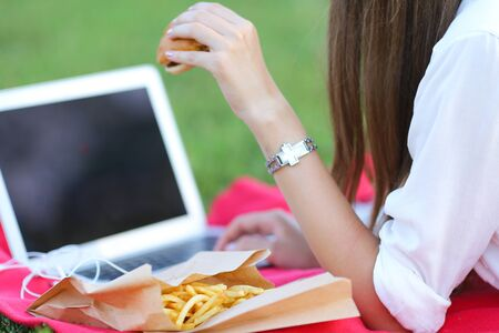 female in the park works behind laptop. beautiful girl with glasses eating fast food in nature and smiling.