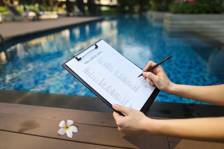 female hand holds out pen, fills out application form in United States. Sunny portrait on pool background And sunlight. concept of traveling to new countries. Front used with Open Font License