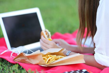 female in the park works behind laptop. beautiful girl with glasses eating fast food in nature and smiling. Reklamní fotografie - 133466958