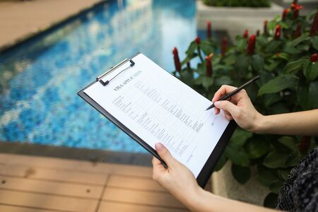 large portrait of womans hand fills out application form for Iceland against pool background. concept of long-term travel to warm countries. Front used with Open Font License
